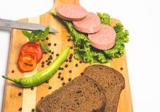 Νόστιμες λουκάνικο και ψωμί με το μαρούλι και ντομάτα για το μεσημεριανό γεύμα και το γεύμα στοκ εικόνες