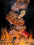Νόστιμες μπριζόλες βόειου κρέατος που πετούν επάνω από τη σχάρα χυτοσιδήρου με τις φλόγες πυρκαγιάς στοκ φωτογραφία με δικαίωμα ελεύθερης χρήσης