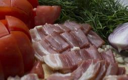 Νόστιμες φέτες του μπέϊκον δίπλα στα λαχανικά στοκ φωτογραφία με δικαίωμα ελεύθερης χρήσης