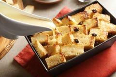 Νόστιμη έκχυση κρέμας στην πουτίγκα ψωμιού με τη σταφίδα Στοκ Φωτογραφίες