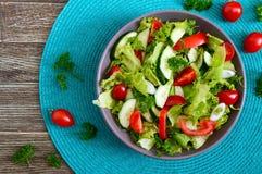 Νόστιμη διαιτητική σαλάτα βιταμινών με τα φρέσκα αγγούρια, ντομάτες, πράσινα Σαλάτα από τα οργανικά λαχανικά r στοκ φωτογραφία με δικαίωμα ελεύθερης χρήσης
