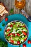 Νόστιμη διαιτητική σαλάτα βιταμινών με τα φρέσκα αγγούρια, ντομάτες, πράσινα Σαλάτα από τα οργανικά λαχανικά r στοκ φωτογραφία