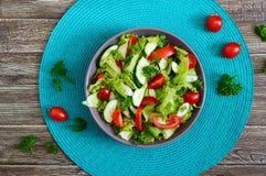 Νόστιμη διαιτητική σαλάτα βιταμινών με τα φρέσκα αγγούρια, ντομάτες, πράσινα Σαλάτα από τα οργανικά λαχανικά r στοκ εικόνες