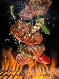 Νόστιμη μπριζόλα βόειου κρέατος που πετά επάνω από τη σχάρα χυτοσιδήρου με τις φλόγες πυρκαγιάς στοκ φωτογραφία με δικαίωμα ελεύθερης χρήσης