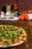 Νόστιμη πίτσα με το arugula και ελιές στον ξύλινο πίνακα και το άλλο VE Στοκ Φωτογραφία