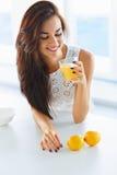 Νόστιμη υγιής γυναίκα προγευμάτων που πίνει το χυμό από πορτοκάλι και το χαμόγελο Στοκ Εικόνες