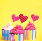 Νόστιμη φράουλα τρία cupcakes στα ζωηρόχρωμα φλυτζάνια ψησίματος εγγράφου, με χρόνια πολλά τη ευχετήρια κάρτα, στο κίτρινο υπόβαθ Στοκ φωτογραφία με δικαίωμα ελεύθερης χρήσης