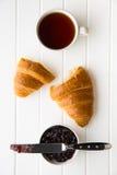 Νόστιμος βουτυρώδης croissant, φλυτζάνι του μαύρου τσαγιού και μαρμελάδα στο βάζο στοκ φωτογραφίες με δικαίωμα ελεύθερης χρήσης