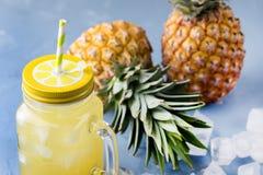 Νόστιμος κοκτέιλ ή χυμός ανανά στο βάζο γυαλιού με άχυρα και δύο ανανάδες σε έναν μπλε κύβο πάγου υποβάθρου στοκ φωτογραφίες