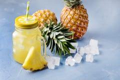Νόστιμος κοκτέιλ ή χυμός ανανά στο βάζο γυαλιού με άχυρα και δύο ανανάδες σε έναν μπλε κύβο πάγου υποβάθρου στοκ εικόνα με δικαίωμα ελεύθερης χρήσης