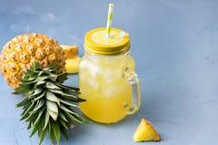 Νόστιμος κοκτέιλ ή χυμός ανανά στο βάζο γυαλιού με άχυρα και δύο ανανάδες σε έναν μπλε κύβο πάγου υποβάθρου στοκ φωτογραφία