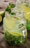 Νόστιμος κρύος φρέσκος πίνει τη λεμονάδα με το λεμόνι, τη μέντα, τον πάγο και τον ασβέστη ι Στοκ Φωτογραφίες