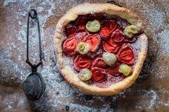 Νόστιμος ξινός με τα φρούτα και ζάχαρη σκονών σε χαρτί ψησίματος στοκ εικόνες