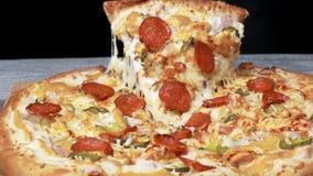 Νόστιμος πάρτε τη φέτα της πίτσας με το τυρί Πλαίσιο Ορεκτικό χωριστό κομμάτι της στρογγυλής πίτσας που τεντώνει το λειωμένο τυρί φιλμ μικρού μήκους