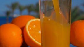 Νόστιμος χυμός από πορτοκάλι κινηματογραφήσεων σε πρώτο πλάνο που χύνεται σε ένα γυαλί απόθεμα βίντεο