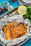 Νόστιμος ψημένος σολομός ψαριών στο φύλλο αλουμινίου στον μπλε πίνακα, τοπ άποψη στοκ εικόνες