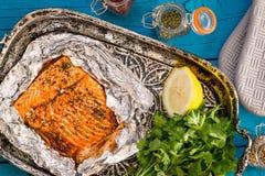Νόστιμος ψημένος σολομός ψαριών στο φύλλο αλουμινίου στον μπλε πίνακα στοκ εικόνες με δικαίωμα ελεύθερης χρήσης
