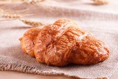 Νόστιμος croissant με τη μαρμελάδα στο αγροτικό υπόβαθρο με spikelets στοκ εικόνα