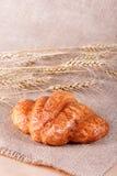 Νόστιμος croissant με τη μαρμελάδα στο αγροτικό υπόβαθρο με spikelets στοκ φωτογραφία με δικαίωμα ελεύθερης χρήσης