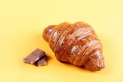 Νόστιμος croissant με τη σοκολάτα και μαρμελάδα στο κίτρινο υπόβαθρο στοκ φωτογραφία