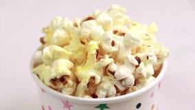 Νόστιμο αλμυρό popcorn στο φλυτζάνι εγγράφου στο ελαφρύ μαρμάρινο υπόβαθρο απόθεμα βίντεο