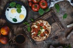 Νόστιμο αρτοποιείο με τις ντομάτες στον ξύλινο δίσκο, τα τηγανισμένα αυγά, τις φρέσκους ντομάτες και τους νεαρούς βλαστούς tablet Στοκ Εικόνα