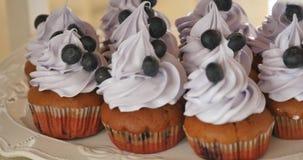 Νόστιμο βακκίνιο cupcakes που διακοσμείται με την κρέμα και τα φρέσκα μούρα απόθεμα βίντεο