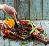 Νόστιμο θρεπτικό γεύμα Χέρια γυναικών που κόβουν την μπριζόλα στο δρύινο SE πινάκων Στοκ Εικόνες