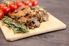 Νόστιμο κρέας χοιρινού κρέατος με τα ψημένα στη σχάρα μανιτάρια δίπλα oregano στον κλάδο Στοκ Εικόνες