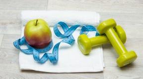 Νόστιμο μήλο, ταινία μέτρου και βάρη στην πετσέτα Στοκ εικόνα με δικαίωμα ελεύθερης χρήσης
