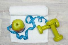 Νόστιμο μήλο, ταινία μέτρου και βάρη στην πετσέτα Στοκ Εικόνα