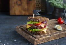 Νόστιμο σάντουιτς φιαγμένο από ψωμί, ντομάτες, λουκάνικο, κρεμμύδι και μαρούλι στο σκοτεινό υπόβαθρο, εκλεκτική εστίαση Στοκ εικόνες με δικαίωμα ελεύθερης χρήσης