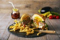 Νόστιμο χάμπουργκερ με τις τηγανιτές πατάτες, εκλεκτική εστίαση Στοκ Φωτογραφία