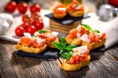Νόστιμο bruschetta με την ντομάτα, βασιλικός, παρμεζάνα, ελαιόλαδο στοκ εικόνα