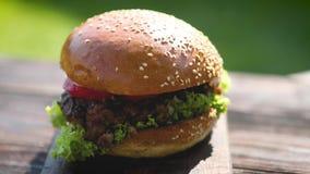 Νόστιμο burger βόειου κρέατος με, το μαρούλι, το κρεμμύδι και οι ντομάτες εξυπηρέτησαν τον υπαίθριο κήπο απόθεμα βίντεο