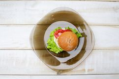 Νόστιμο burger γρήγορου γεύματος στο πιάτο γυαλιού στον ξύλινο πίνακα Στοκ φωτογραφίες με δικαίωμα ελεύθερης χρήσης