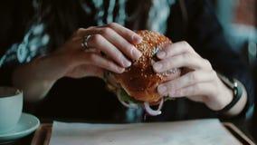 Νόστιμο burger είναι μεγάλο σε έναν ξύλινο δίσκο Μια γυναίκα παίρνει τα χέρια του και επρόκειτο να φάει απόθεμα βίντεο