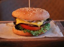 Νόστιμο burger με το βόειο κρέας, την ντομάτα, το τυρί, το κρεμμύδι και το μαρούλι στοκ φωτογραφία με δικαίωμα ελεύθερης χρήσης