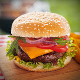 Νόστιμο burger με το λειωμένο τυρί σε ένα κουλούρι σουσαμιού Στοκ Εικόνες