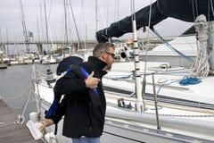 Νότια Καρολίνα μαρινών του Τσάρλεστον, στις 17 Φεβρουαρίου 2018 - άτομο που αγωνίζεται να βάλει στο σακάκι ζωής δίπλα sailboat στ Στοκ Εικόνα