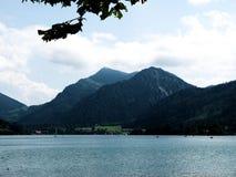 Νότιο γερμανικό τοπίο με τα βουνά και λίμνη με τις βάρκες στοκ εικόνα