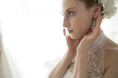 Νύφη για να σιγουρευτεί τα σκουλαρίκια Στοκ Εικόνες