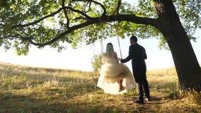 Νύφη και γύρος νεόνυμφων στην ταλάντευση στο πάρκο ευτυχής ερωτευμένη ταλάντευση ζευγών στην ταλάντευση στο δάσος απόθεμα βίντεο