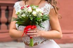 Νύφη και δύο νύφες κρατούν τις γαμήλιες ανθοδέσμες τους, που παρουσιάζουν τις στοκ εικόνα