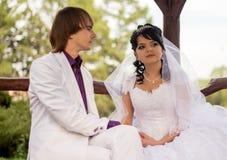 Νύφη και νεόνυμφος αγάπης ζεύγους που θέτουν τη συνεδρίαση επάνω Στοκ Φωτογραφία