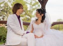 Νύφη και νεόνυμφος αγάπης ζεύγους που θέτουν τη συνεδρίαση επάνω Στοκ εικόνες με δικαίωμα ελεύθερης χρήσης