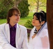 Νύφη και νεόνυμφος αγάπης ζεύγους που θέτουν τη συνεδρίαση επάνω Στοκ Εικόνες