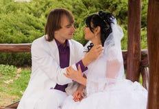 Νύφη και νεόνυμφος αγάπης ζεύγους που θέτουν τη συνεδρίαση επάνω Στοκ εικόνα με δικαίωμα ελεύθερης χρήσης