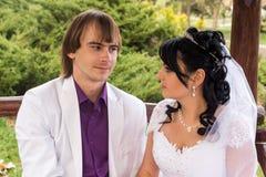 Νύφη και νεόνυμφος αγάπης ζεύγους που θέτουν τη συνεδρίαση επάνω Στοκ φωτογραφίες με δικαίωμα ελεύθερης χρήσης
