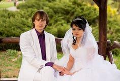 Νύφη και νεόνυμφος αγάπης ζεύγους που θέτουν τη συνεδρίαση επάνω Στοκ φωτογραφία με δικαίωμα ελεύθερης χρήσης